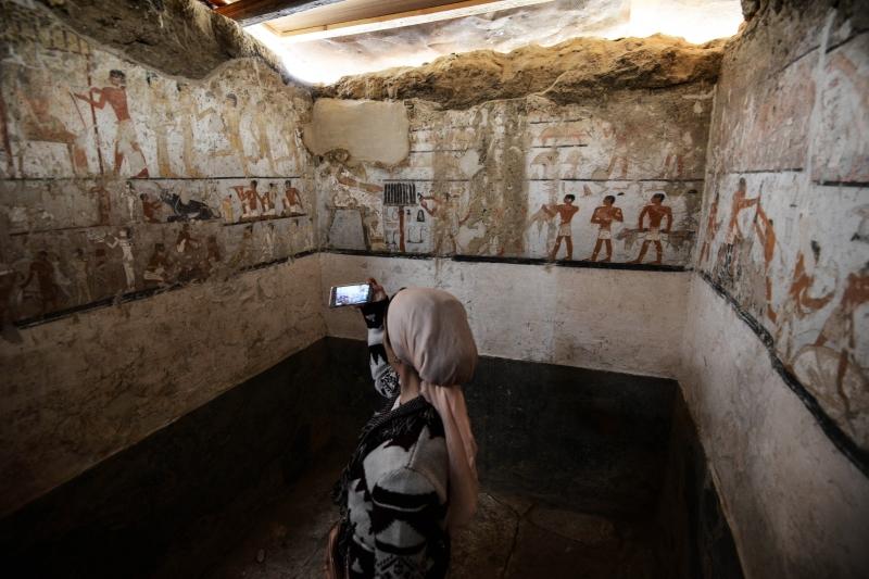 Mulher registra no celular imagens das pinturas que estão nas paredes de tumba decoberta