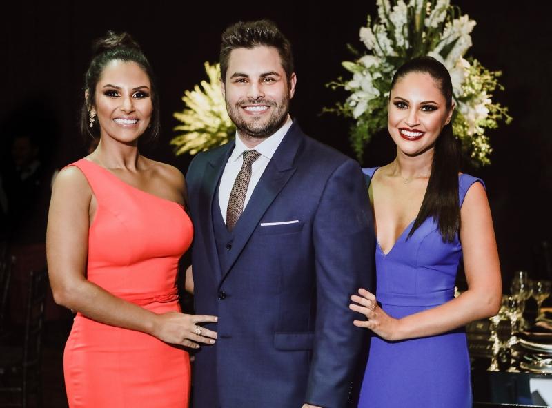 Formando Aloir Neri de Oliveira Júnior entre as irmãs Mayara e Thairine Reis de Oliveira