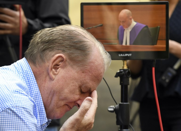 A man reacts as he listens to County Court Chief Judge Peter Kidd (on the monitor) speak during the sentencing of Cardinal George Pell who was was found guilty on historic child sex crimes, in Melbourne on March 13, 2019. (Photo by William WEST / AFP)