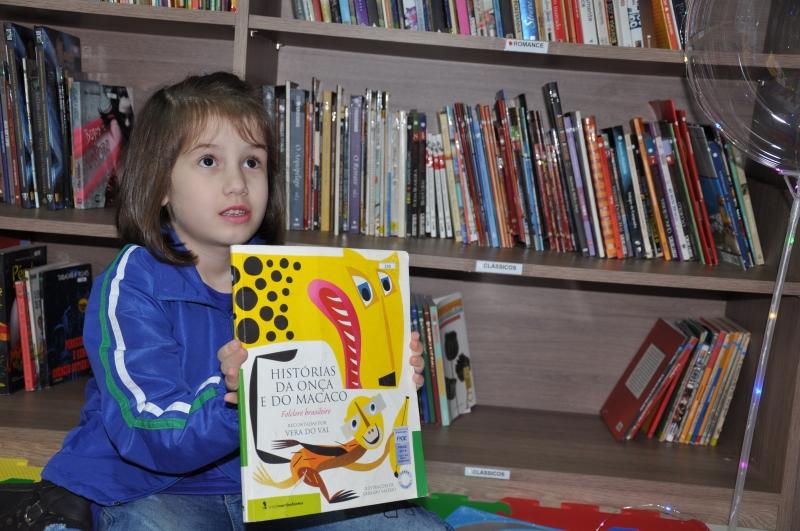 Crianças e adolescentes podem pegar livros para ler, e professoras também contam histórias aos pequenos
