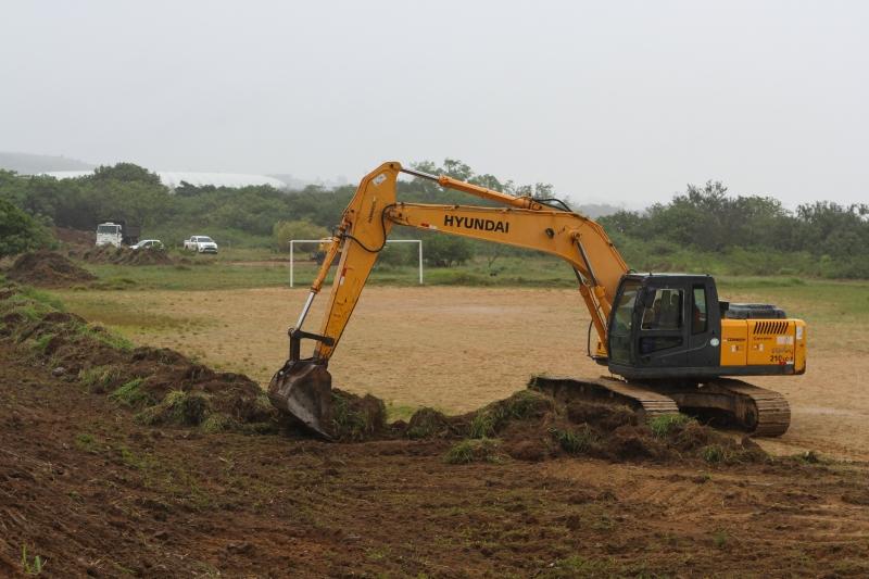 Retroescavadeira retira vegetação para preparar a área para receber o aterro previsto no projeto
