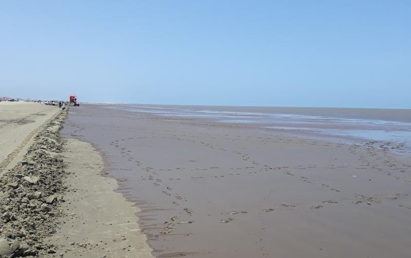 Na areia, uma fina camada de lama marrom, que parece um filme, marca o impacto do material
