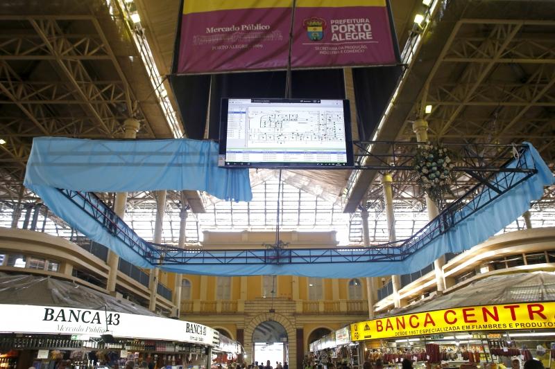 Painel fica suspenso na área central do mercado; cor verde indica que está tudo normal