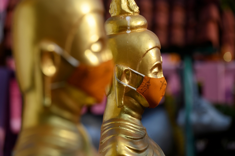 Buddha statues wearing face masks, in response to the current COVID-19 novel coronavirus situation, are seen at Wat Nithet Rat Pradit temple in Pathum Thani outside Bangkok on May 12, 2020. (Photo by Mladen ANTONOV / AFP)