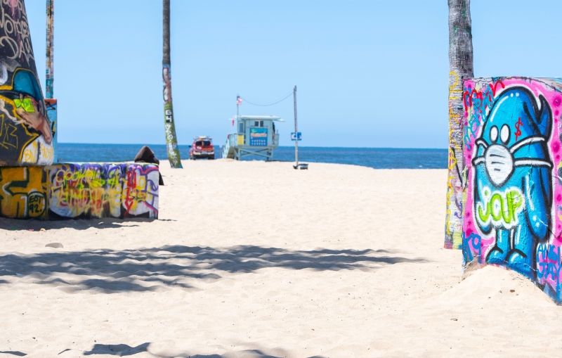 View of a graffiti of a person with a mask  in Venice Beach, california on the first day Los Angeles County allowed beaches to reopen after a six-week closure implemented to stop the spread of the coronavirus (Covid-19),on May 13, 2020. - The County only allows activities such as running, walking, swimming and surfing with sunbathing and volleyball not allowed. (Photo by VALERIE MACON / AFP)