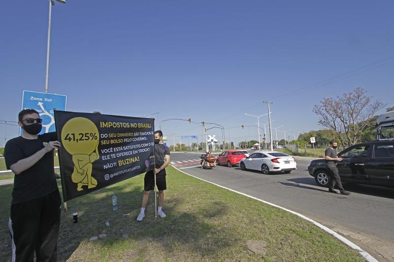 Representantes estão em sinaleiras e caminhando pela Orla do Guaíba distribuindo flyers