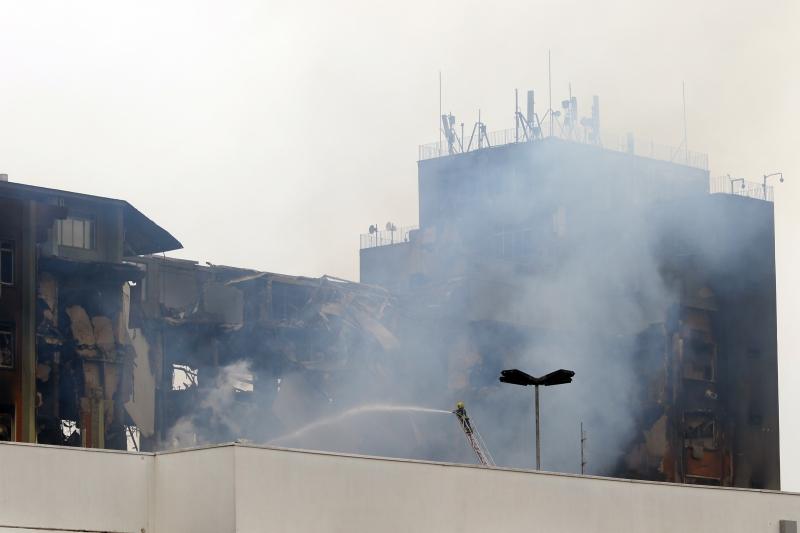 Equipes trabalham no prédio da Secretaria de Segurança Pública, que foi destruído após incêndio na noite de quarta-feira
