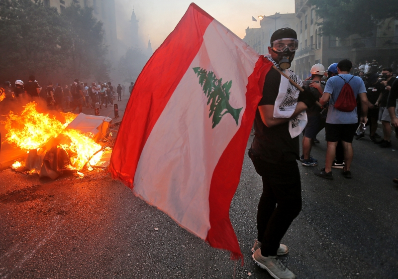 A protester stands with a Lebanese national flag during clashes with army and security forces near the Lebanese parliament headquarters in the centre of the capital Beirut on August 4, 2021, on the first anniversary of the blast that ravaged the port and the city. - Hundreds of Lebanese marched on August 4 to mark a year since a cataclysmic explosion ravaged Beirut, protesting impunity over the country's worst peacetime disaster at a time when its economy was already in tatters. (Photo by - / AFP)       Caption