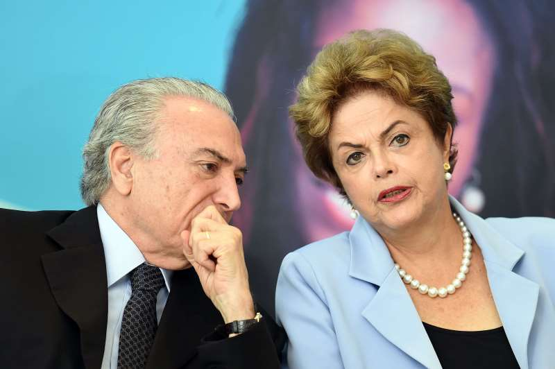 BRAZILIAN PRESIDENT DILMA ROUSSEFF (R) AND VICE-PRESIDENT MICHEL TEMER ATTEND THE LAUNCHING CEREMONY OF THE INVESTMENT PROGRAM IN ENERGY AT PLANALTO PALACE IN BRASILIA, ON AUGUST 11, 2015. ANALYSTS SAY BRAZIL'S ONCE BOOMING ECONOMY SUFFERS DEEP UNDERLYING ILLNESSES, NOTABLY THE MASSIVE CORRUPTION SCANDAL UNFOLDING AT NATIONAL OIL COMPANY PETROBRAS AND RIPPLING ACROSS OTHER TOP COMPANIES AND INTO POLITICAL CIRCLES. IT IS ALSO ON THE BRINK OF RECESSION. ACCORDING TO A RECENT POLL THAT PUT ROUSSEFF'S APPROVAL RATING AT EIGHT PERCENT, SHE IS NOW BRAZIL'S MOST UNPOPULAR DEMOCRATICALLY ELECTED PRESIDENT SINCE A MILITARY DICTATORSHIP ENDED IN 1985.   AFP PHOTO / EVARISTO SA