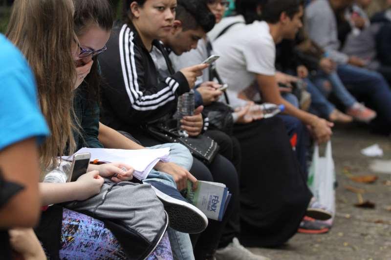 Enem 2º dia antes do início das provas.  Segundo dia de provas do enem é marcado pela redação. Na PUC de Porto Alegre onde há grande concentração de candidatos para  o concurso o movimeno foi intenso.  Na foto: Candidatos aguardam o horário de ingressar no prédio para realizar as provas. Estudantes, Estudo, Alunos, leitura,