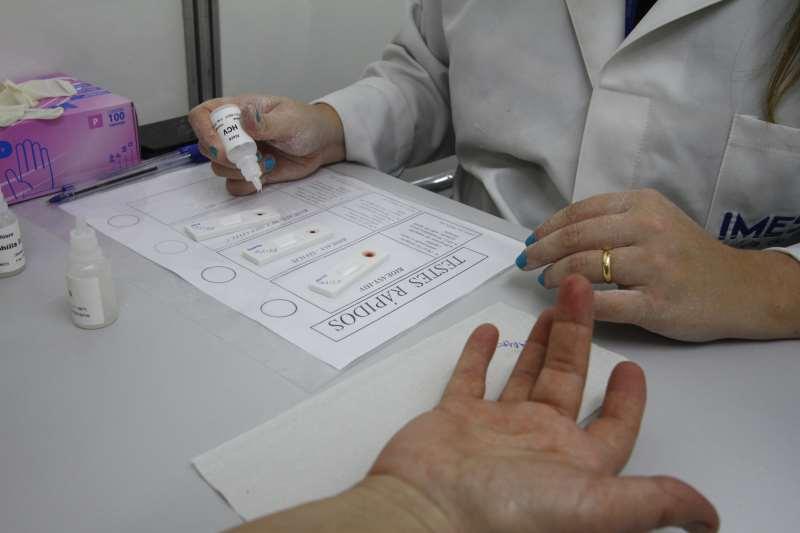 Com um aparelho, gotas de sangue são coletadas e colocadas em contato com um reagente. O resultado fica pronto em 20 minutos