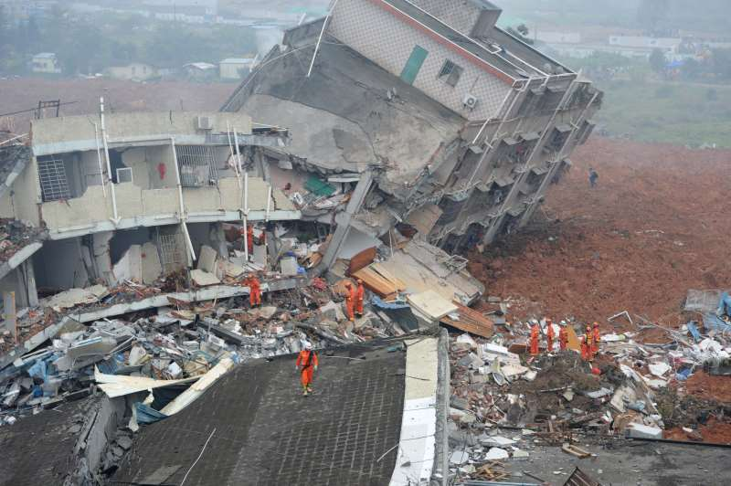 int - deslizamento de terra na china   TOPSHOT - Rescuers look for survivors after a landslide hit an industrial park in Shenzhen, south China's Guangdong province on December 20, 2015. A massive landslide at an industrial park in southern China buried 22 buildings and left 22  people missing on December 20, state media reported, as more than 1,500 emergency workers searched the scene. CHINA OUT   AFP PHOTO / AFP / STR