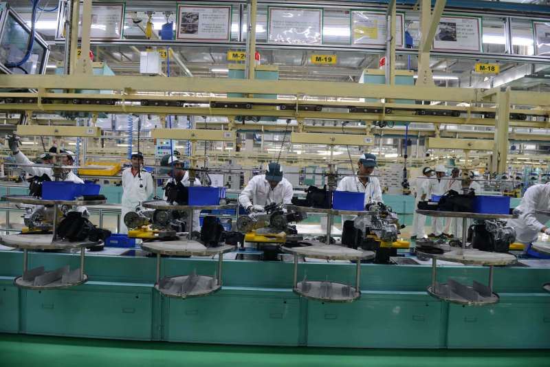 Workers are pictured on the assembly line of Activa scooters at the new plant of Honda Motorcycle and Scooter India Pvt Ltd (HSMI) in Vithalapur, some 80 km from Ahmedabad on February 17, 2016. / AFP / SAM PANTHAKY