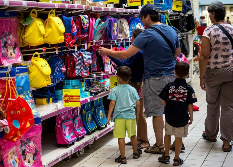 People buy school supplies with their children on August 18, 2016 at a supermarket in Englos, northen France, ahead of the start of the new school year.   The average back-to-school costs will remain stable this year, at 190,24 euros for a child entering the first year of secondary school, revealed the Familles de France on August 17, 2016. / AFP PHOTO / PHILIPPE HUGUEN