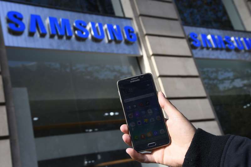 A person holds up a Samsung smart phone in front of the Samsung store in Paris on October 11, 2016.  Samsung on October 11 pulled the final plug on its troubled Galaxy Note 7 smartphone, permanently discontinuing production of the flagship device that has been mired in a disastrous recall over exploding batteries. / AFP PHOTO / BERTRAND GUAY